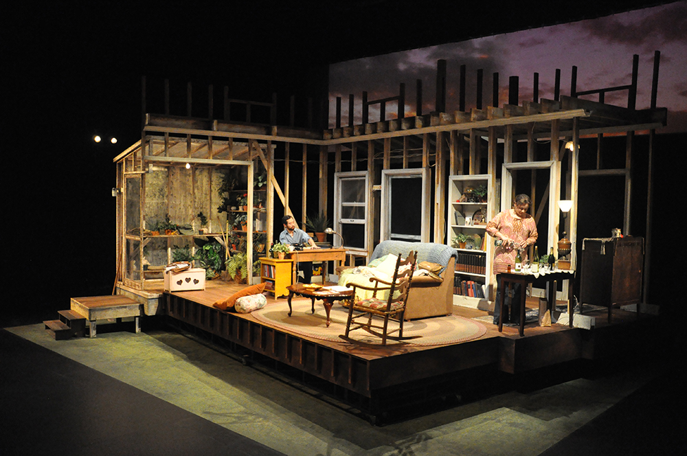 A set for The Fifth of July shows the interior of a home with a sky backdrop