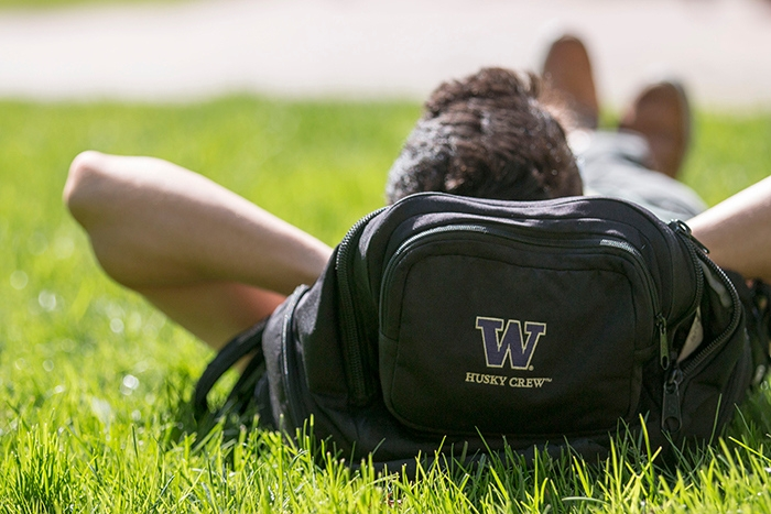 Student reclines on backpack on a sunny day