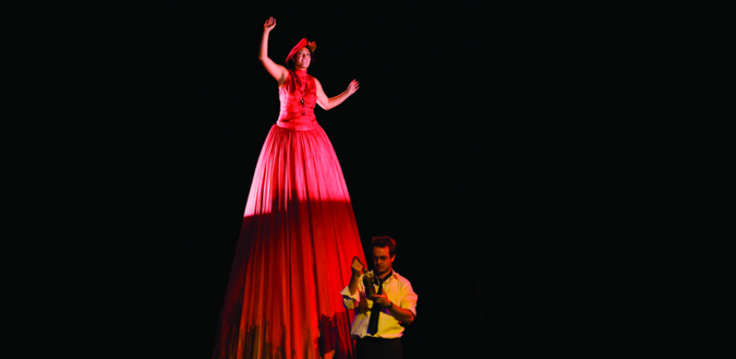 "An actor appears in an extremely tall red dress in the play ""Harp Song for a Radical"""