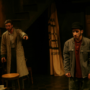 A man in a housecoat points to a man in a jacket.