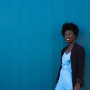 Nikki Yeboah stands against a blue backgrou
