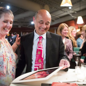 Ruben Van Kempen, with a former student, at a party celebrating his retirement and raising funds to support the Roosevelt High Drama program. (Lindsey Wasson / The Seattle Times)
