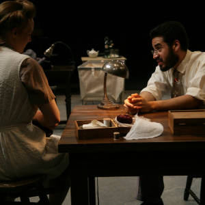 Two actors sit at a table, a woman facing away from the shot, a male leaning onto the table.