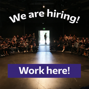 """A photo of the inside of a theatre with people in the seats and the words """"We are hiring! Work here!"""" overlaid"""