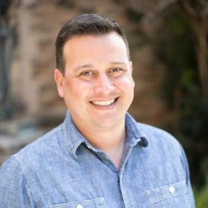 Ryan smiling outside in denim shirt.