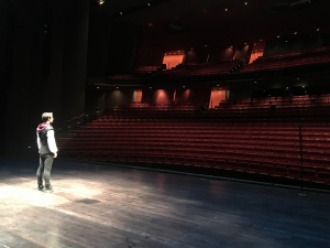 student on Meany stage facing an empty theater
