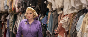 Portrait of Chante Hamann, standing in one of the School of Drama's storage rooms for costumes.