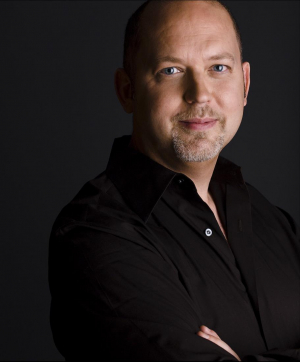 This is an image of Jeff Caldwell. He is staring and smiling at the camera. He is wearing a black shirt and folding his arms.