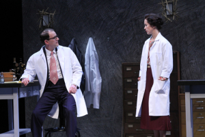 A man in a lab coat at a desk turns to talk to a woman in a labcoat.