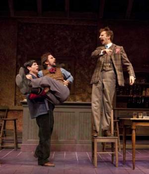 A man on top of a chair yells down at a man in another man's arms