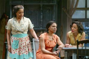 Three women sit in a kitchen in the 1950's