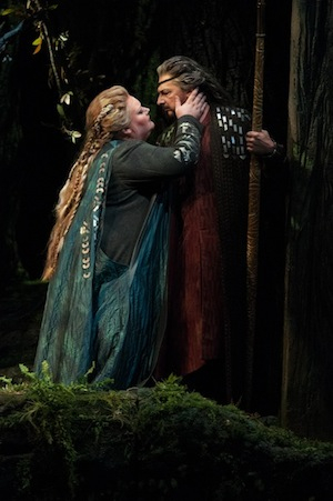 A Woman in blue leans in towards and rests her hand on a man's face who looks back at her amid a forestry surrounding.