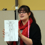 Picture of Jocelyn Fowler (BA '09) with one of her costume sketches.