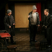 MacHeath talks with two of the henchmen, who areholding a bat and keys.