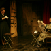 Mr. Peachum reads the newspaper while Mrs. Peachum smiles at him with a cup of coffee.