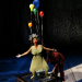 A strange faced woman has balloons come out from her while standing on a table.
