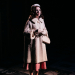 Woman in coat on stage.