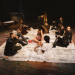 Actors sit on a blanket on the floor