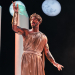 Actor in toga stands onstage with moon in background