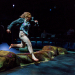 Woman jumps over log onstage